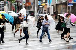 台風19号の接近で強まる風雨にさらされながら、横断歩道を渡る人たち=12日午前10時22分、神戸市中央区(撮影・中西幸大)