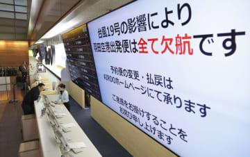 台風19号の接近で、羽田空港を発着する全便が欠航になったことを伝える航空会社のモニター=12日午前8時2分