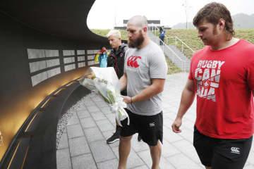 小雨の降る中、追悼施設「釜石祈りのパーク」を訪れ、献花するカナダ代表の選手ら=12日、岩手県釜石市