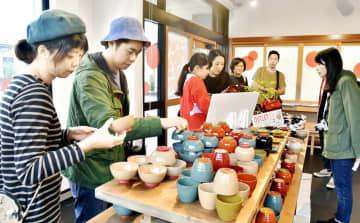 カラフルな漆器製品を手に取る来場者=10月12日、福井県鯖江市西袋町