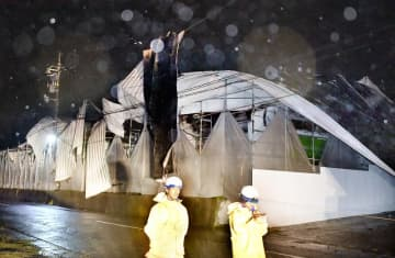 台風19号の強風でめくれた屋根が電線に引っ掛かった繊維工場建物=10月12日午後8時50分ごろ、福井県永平寺町松岡石舟