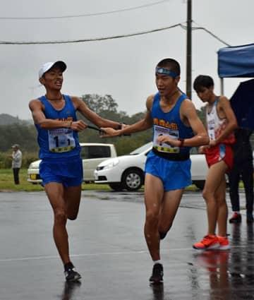 【男子】青森山田1区・成田(左)からたすきを受け、走りだす2区・青木