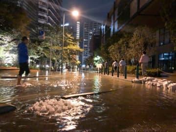 水が路面に噴き出し、辺り一帯が冠水した武蔵小杉駅東口付近=13日午前0時半ごろ、川崎市中原区新丸子東3丁目