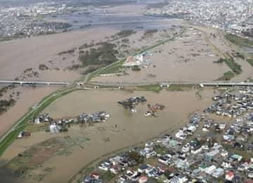 浸水した信濃川右岸の長岡市今井、大宮町付近。中央の橋はフェニックス大橋=13日午後0時30分すぎ(本社ヘリから)