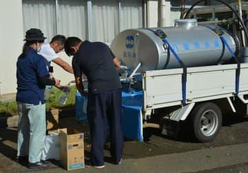 市立川上小学校で給水に訪れた住民らの容器に水を注ぐ市職員=13日午前8時45分ごろ、八街市