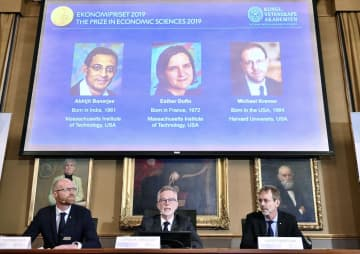 ノーベル経済学賞の受賞者を発表するスウェーデン王立科学アカデミーの記者会見=14日、ストックホルム(ロイター=共同)