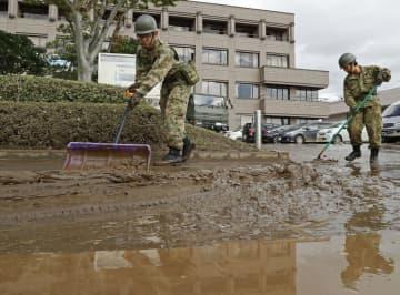 宮城県丸森町の役場前で土砂の撤去作業をする自衛隊員=15日午前10時15分