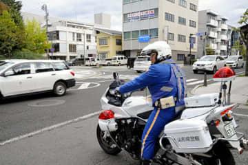 白バイも投入し、渡ろうとする歩行者がいても停車しない運転者を集中的に取り締まった=山形市内