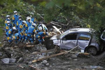 宮城県丸森町廻倉地区の土砂崩れ現場で車を捜索する警察官=15日午後3時28分