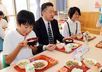 生産者(中央)と給食を味わう児童ら=高岡市福岡小学校