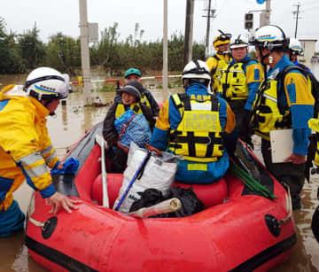 長野市内でゴムボートを使って被災者を救助する広島県警の警察官(県警提供)