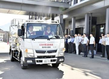 職員に見守られながら福島県相馬市へ出発する給水タンク車=10月15日、福井県の大野市役所