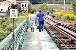 水郡線の鉄橋を渡り物資などを運ぶ町民ら=矢祭町