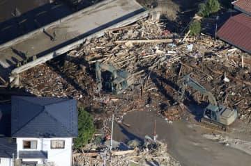 宮城県丸森町の川で押し寄せた流木などの除去作業をする自衛隊員=16日午後2時39分(共同通信社ヘリから)