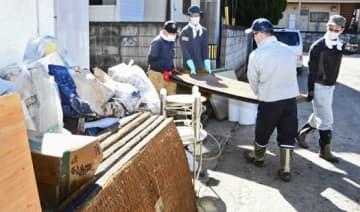 釈迦堂川の氾濫で浸水した須賀川市中宿の住宅から畳を運び出すボランティア=16日午前11時25分ごろ