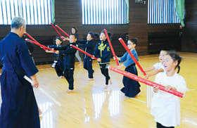 棒を使って竹刀の振り方を学ぶ子ども