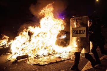 16日、スペインの州都バルセロナで、デモ隊と警官隊が衝突し、燃えるバリケードに突っ込んだ警察車両から離れる警察官(AP=共同)