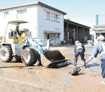 団地内に厚く積もった泥をかき出す事業者ら=16日午前11時25分ごろ、郡山市の中央工業団地