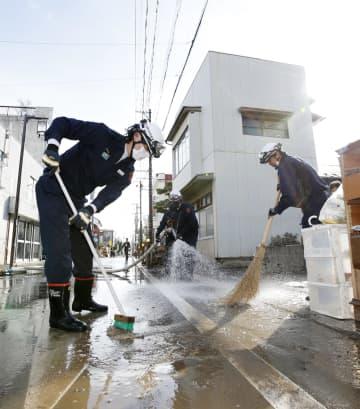 道路を掃除する消防団員=17日午後、福島県本宮市