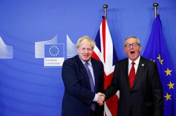 握手するジョンソン英首相(左)とEUのユンケル欧州委員長=ブリュッセル(ロイター=共同)