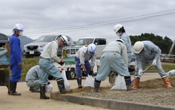復旧作業中の浄水場への被害防止に向け、土のうを準備する作業員ら=18日午前、福島県いわき市