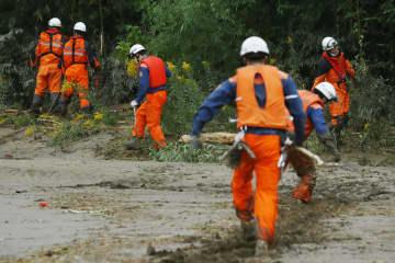 宮城県丸森町内を流れる川周辺を捜索する消防隊員=18日午前