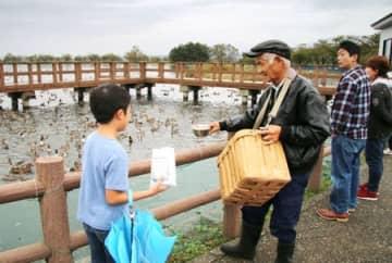 おなじみの格好で白鳥やカモに餌をまく斎藤功さん=阿賀野市水原