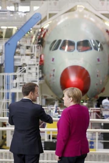 フランス南部トゥールーズにあるエアバスの工場を視察するマクロン大統領(左)とドイツのメルケル首相=16日(ロイター=共同)