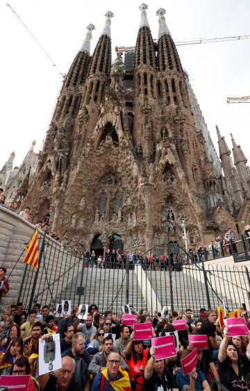 スペイン・バルセロナのサグラダ・ファミリア教会前でスローガンを叫ぶデモ参加者=18日(ロイター=共同)