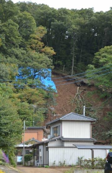 山肌がむき出しになった土砂崩れ現場。付近の住民に避難勧告が出されている=20日午後、足利市助戸大橋町