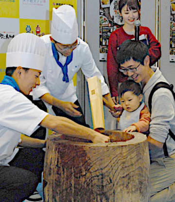 餅つきを体験する家族=20日、米子コンベンションセンター