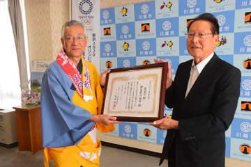 「日本の祭り」の選定の証を持つ川合善明市長(左)と日本の祭りネットワークの高松富博理事長(ダイドードリンコ会長)=20日午前、川越市役所