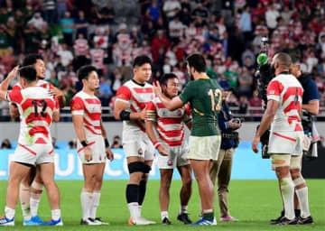 試合後、南アフリカの選手と健闘をたたえ合う日本の流大(中央)=20日、東京都の味の素スタジアム(小野宏明)