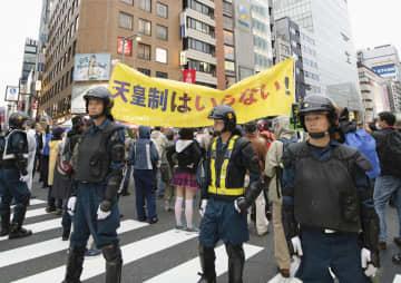 天皇制に反対しデモ行進する人たちと警戒に当たる機動隊員=22日午後、東京都中央区