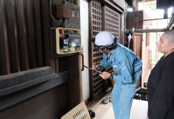 本堂の配電盤を点検する京都電業協会の会員(左)=京都市中京区