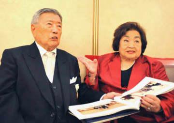 即位礼正殿の儀に参列後、記念品の写真集を手にする柴田さん(左)とサーローさん