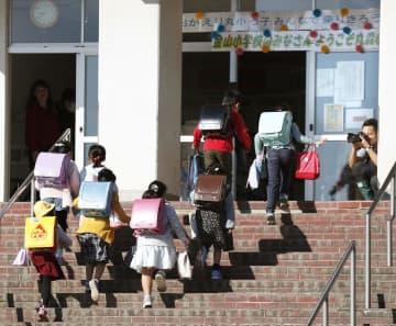 再開した丸森小学校に登校する児童=23日午前、宮城県丸森町