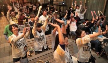 日本シリーズを制し、万歳して喜ぶホークスファン=23日午後、宮崎市・宮崎山形屋四季ふれあいモール