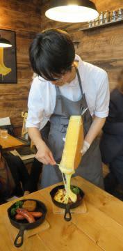 料理にラクレットチーズをかける店員=守谷市松ケ丘の「Cheese Cheers Cafe」