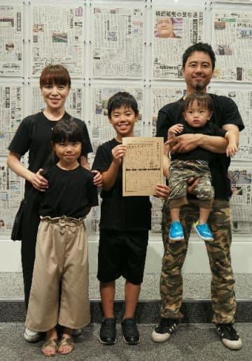 家族5人で展示会場を訪れ、気持ちを新たにする高村君(中央)=5日、横浜市の日本新聞博物館