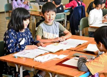 緑ケ丘一小の教室で、国語の勉強をする永盛小の児童。授業再開の初日、一つの教科書を2人で使う場面もあった
