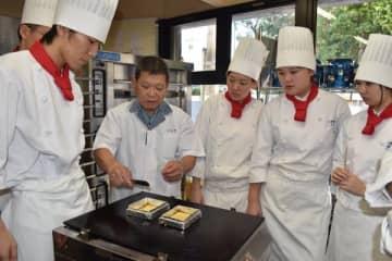 【焼いた皮を裏返すタイミングを生徒に指導する長井さん(左から2人目)=津市大谷町の三重調理専門学校で】
