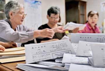 親の会通信を封筒に入れる作業をするスタッフ=長崎市出来大工町、親の会事務所