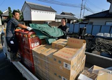 駐車場内に泥が残る中、出荷作業を進める従業員ら=23日午前8時40分、佐野市田島町