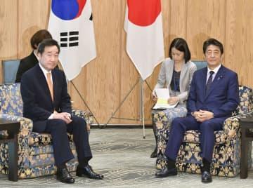 会談に臨む韓国の李洛淵首相(左)と安倍首相=24日午前、首相官邸