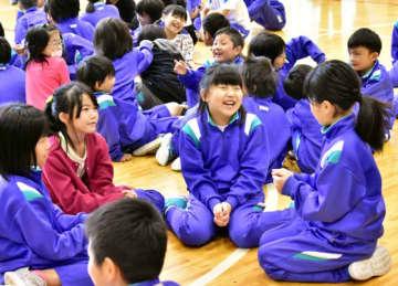 11日ぶりの学校再開に、友人と笑顔で会話する重茂小児童=23日午前7時50分、宮古市重茂