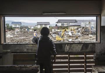 浸水被害を受け、ガラスを外した実家の窓から外を見る女性。「元々どんな風景だったかも分からなくなっちゃうね」とつぶやいた=24日午前、長野市