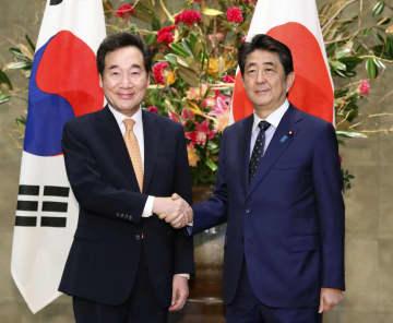 会談前に握手する韓国の李洛淵首相(左)と安倍首相=24日、首相官邸