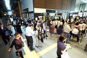 東京方面行きの切符を買い求める客で混雑する構内=24日午前11時31分、JR富山駅