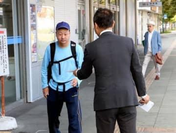 防府市のJR防府駅前で政策を書いたチラシを配り支援を呼び掛ける衆院山口1区の立候補予定者(手前)
